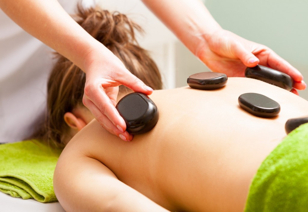 Day-spa. Young woman in green towel relaxing in healthy spa salon. Girl having hot stone massage. Indoor.